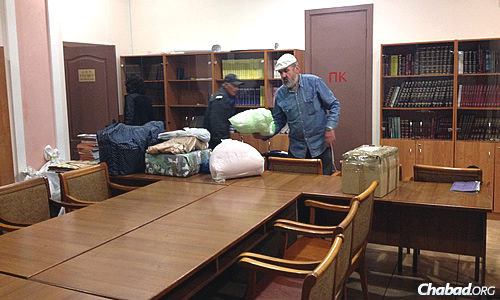 Volunteers bring the newly arrived supplies into the community's temporary synagogue space in Kiev. (Photo: Dovid Margolin)