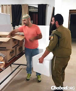 Volunteers in Sderot help package food for the needy. (Photo: Colel Chabad)