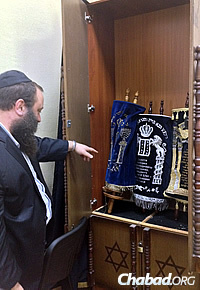 Rabbi Levi Raices, who heads the Yeshiva Ketana in Kharkov, points to Torah scrolls that were recently brought out of Lugansk and are being held at the yeshivah for safekeeping.
