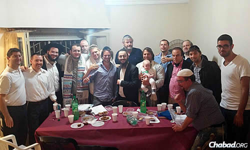 "Worshippers at the ""break fast"" meal following the conclusion of Yom Kippur (Levy is standing, third from left; Setton is standing in the center)."