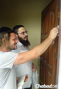 Setton helps affix a mezuzah on a Jewish resident's home before the start of Yom Kippur.