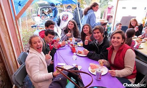 Os estudantes almoçam na sucá.