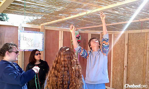 Teens finalize the roof with its sechach on top.