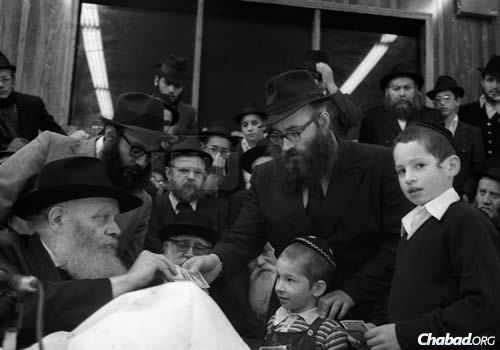 Rabbi Azimov receiving a dollar and a blessing from the Lubavitcher Rebbe. (Photo: JEM/The Living Archive)