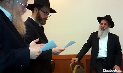 """Marc Shudnow, 45, center, recently participated in his own """"pidyon haben""""—or """"redemption of the [firstborn] son""""—ceremony since it had not been done for him as a baby. With him are the Kohen, Dovid Grinker, left, who presided over the ceremony, and, far right, Rabbi Yosef Posner, director of Lubavitch Chabad of Skokie, Ill."""