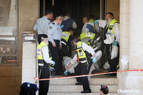 Les sauveteurs israéliens sortent les corps des victimes assassinées par deux terroristes armés qui ont fait irruption dans la synagogue Kehilat Yaakov du quartier de Har Nof à Jérusalem. (Photo: Noam Revkin Fenton/Flash90)