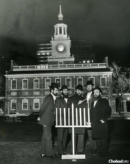 Rabbi Abraham Shemtov, right, in front of Independence Hall in Philadelphia, lighting the very first public menorah in 1974. With him were yeshivah students who helped build the wooden menorah from scratch. (Photo: Lubavitcher Center)