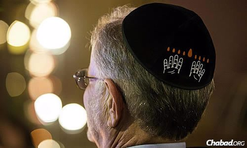 "The logo for the celebrations can be seen on this yarmulke: the ASL word for ""Chanukah,"" formed by two raised hands each with four fingers extended upward, topped by eight flames."