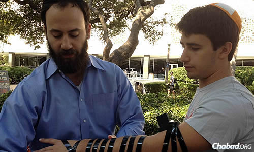 Johnson helps a student wrap tefillin on campus.