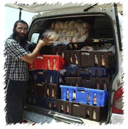 A Colel Chabad employee loads a van with Pitas, to deliver to those that are stranded in their homes in Safed, with all stores closed and not where to purchase basic necessities