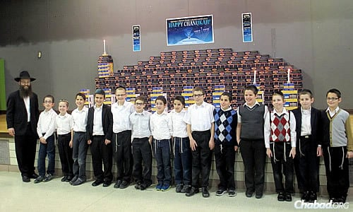 Led by Rabbi Abraham Varnai, fourth-graders at Seymour J. Abrams Cheder Lubavitch Hebrew Day School in Skokie, Ill., build a giant menorah this year made out of other menorahs. honoring the memory of Rabbi Daniel Moscowitz.