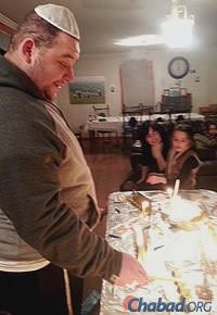 Walz lights a menorah Saturday night in the home of Rabbi Yosef and Yehudis Wolvovsky.