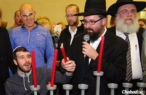 "It was a Chanukah to remember for recovering Sgt. Ohad Benyishai, shown here holding the ""shamash"" (helper candle) to light the menorah."