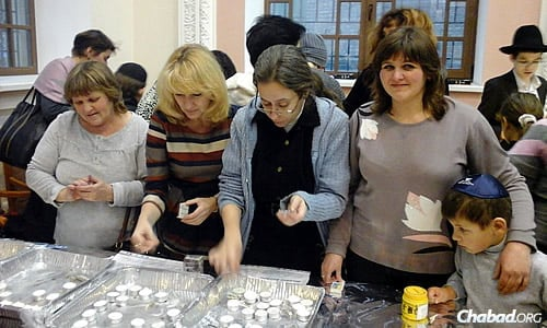 Women light candles before the arrival of Shabbat.