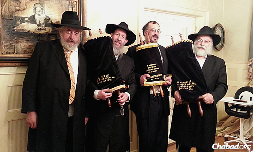 These Torahs were commissioned in honor of the three Israeli teenage boys abducted and killed by Palestinians in June 2014. Holding them, from left, are Yankel Yankelowitz; Bentzion Chanowitz, who runs the Torah Gemach, a project of Merkos Suite 302; Yerachmiel Paskin; and sofer (Torah scribe) Rabbi Daniel Dovid Dahan.