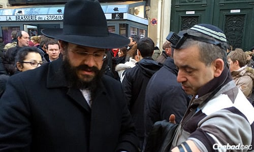 In the midst of the crowd, Chabad-Lubavitch emissaries, students and volunteers were out in full force. Here, Rabbi Yosef Yitzchok Amar wraps tefillin with a man in the crowd.