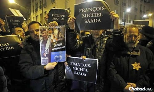 """Citizens show solidarity with the four Jewish men killed in the grocery attack, including signs that read: """"Je Suis Hyper Cacher."""""""