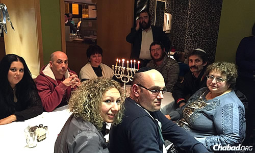Rabbi Sholom Gopin, standing in center, chief rabbi and Chabad emissary of Lugansk, Ukraine, spends time in Ashdod, Israel, during Chanukah with former members of his community who left because of the war back home.