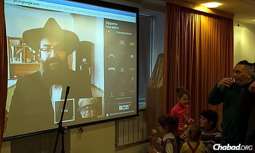 Rabbi Pinchas Vishedski, co-director of Chabad-Lubavitch of Donetsk and the eastern city's chief rabbi, who was out of the country visiting dispersed members of the Donetsk Jewish community, addresses the crowd back home on Google-plus.