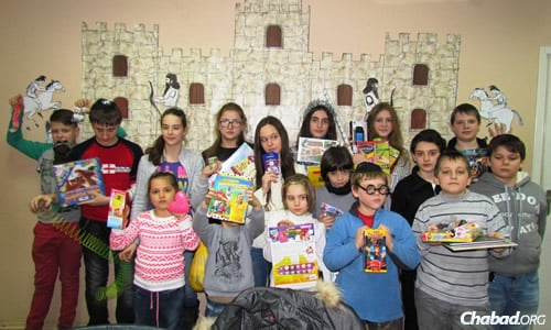 Kids at the Jewish after-school program in Mariupol show off their Chanukah presents.