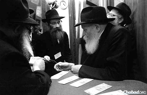 Rabbi Meir Roness, center, receives a dollar from the Rebbe, Rabbi Menachem M. Schneerson, of righteous memory.
