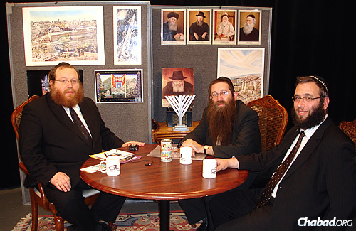 "Rabbi Yosef Katzman, left, has hosted ""A Cable to Jewish Life"" show since 1992. Here, he interviews two Chabad-Lubavitch emissaries—Rabbi Yossi Turk from Cordoba, Argentina, and, on right, Rabbi Mendel Kastel from Sydney, Australia."