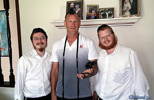 Sharfstein, left, and Lefkowitz wrap tefillin with Mark Margolis in Aberdeen.