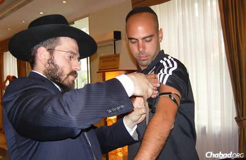 """הרב אליעזר גוראריה מסייע ליהודי להניח תפילין. """"הנקמה הטובה ביותר"""""""