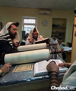 Chabad Rabbi Mendel Cohen, the city's rabbi, reads Torah in Mariupol's synagogue. Rabbi Aaron Kaganovsky, who has taken over some of the shul's daily operations, is to his right.