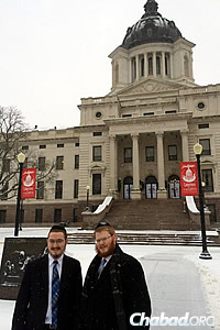 "Outside Pierre's Capitol building during Chanukah 2013. Sharfstein is joined by Rabbi Shmuel Lefkowitz, right. The two ""Roving Rabbis"" have traveled much of the state together visiting Jewish homes."