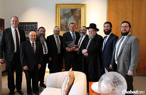 Representatives of the Organisation of Rabbis of Australasia converged in Canberra last week to meet the Australian prime minister, the Hon. Tony Abbott MP, who is holding a menorah presented to him by the group. From left are: Rabbi Paul Lewin, Rabbi Chaim Ingram, Rabbi Moshe Gutnick, Rabbi Yehoram Ulman, Abbott, Rabbi Meir Shlomo Kluwgant, Rabbi Pinchus Feldman, Rabbi Yaakov Glasman and Rabbi Shmuel Feldman. (Photo: Sithu Tin-Aung)