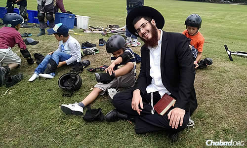 Edan Hanoukah with kids changing out of their sports gear after time on scooters. In addition to athletics, the program includes daily study and prayer sessions.