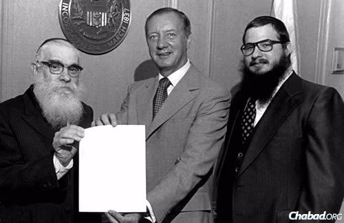 Rabbi Moscowitz, right, came to his hometown of Chicago in 1976 to assist Rabbi Solomon S. Hecht, left, head Chabad emissary of Illinois. Here, they are shown with Michael Anthony Bilandic, the 49th mayor of Chicago and former Chief Justice of the Illinois Supreme Court.