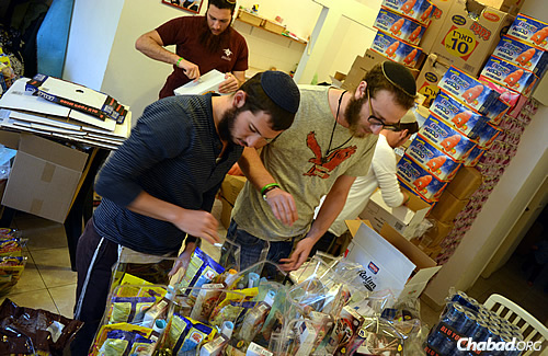 """Packing up food gifts to be sent to """"lone soldiers"""" in the Israeli Defense Forces, as part of this year's Purim project run by the Chayal el Chayal (""""Soldier to Soldier"""") organization."""