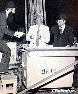Rabbi Tzvi Grunblatt, director of Chabad of Argentina, hands materials to David Goldberg, president of the Jewish umbrella organization DAIA, to light the Chanukah candles on the first public menorah in Buenos Aires in 1985. At right is Israeli ambassador to Argentina Dr. Efraim Tari.