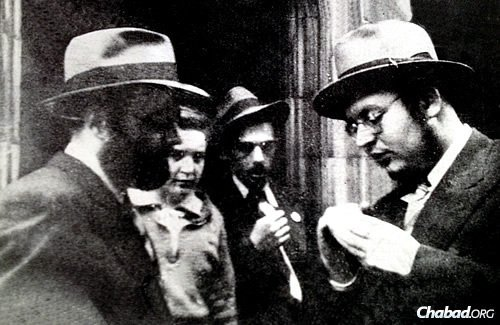 Standing at the front door of 770 Eastern Parkway (the world headquarters of the Chabad-Lubavitch movement), yeshivah student Berel Baumgarten, right, shows the Rebbe—Rabbi Menachem M. Schneerson, of righteous memory—a pin specially created for the Mesibos Shabbos group to encourage Shabbat observance. This picture was taken in 1942, eight years before the Rebbe would accept the mantle of Chabad leadership.