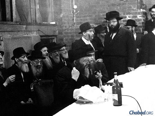 Rabbi Berel Baumgarten, standing, top right, listens as the Rebbe speaks at a farbrengen gathering at 770 Eastern Parkway, Lubavitch World Headquarters, in the early 1960s.