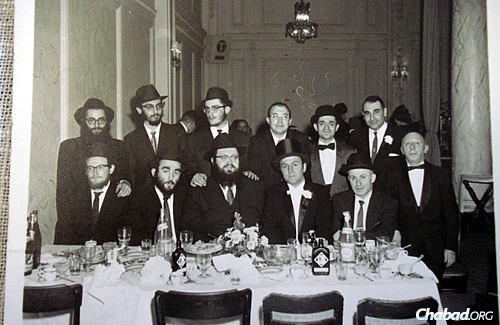 Baumgarten, seated third from left, poses together with his table at what appears to be a wedding celebration.
