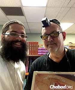 "Rabbi Chayim Mishulovin, left, who runs the Chabad store ""Everything Jewish"" in Portland, Ore., with Eric Patton of North Portland, who came to buy Passover supplies and wound up wrapping tefillin for the very first time."