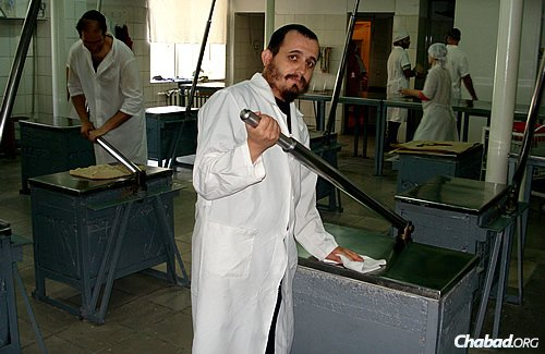 A worker cleans one of the stainless-steel kneading stations at the Dnepropetrovsk matzah bakery.