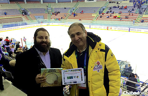 Rafael Pinchasov breaks for matzah at a hockey game, while he displays a book on the history of the Deaflympics.
