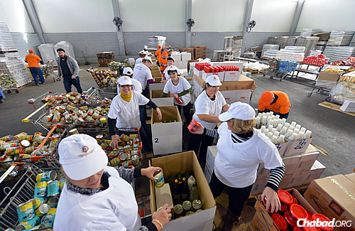 Volunteers pack up boxes of kosher-for-Passover items as part of Colel Chabad's largest food drive to date, which will be distributed to those in need in time for the holiday. (Photo: Israel Bardugo)