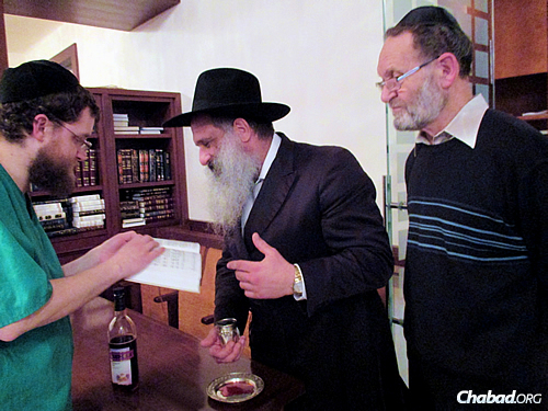 The mohel, Mordechai Tzvi Salamon, left, with the rabbi and Pasternak