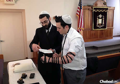 Rabbi Yehuda Ceitlin, outreach director of Chabad Lubavitch of Tucson and associate director of Congregation Young Israel-Chabad, wraps tefillin with Justin Schecker, a reporter for KGUN 9 television news.