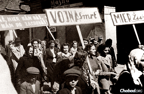 Pasternak's mother can be seen in the center, holding a sign, in the city of Prešov after the war.