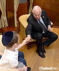 The president handed all three kids pieces of kosher chocolate. (Photo: Mark Neiman/GPO)