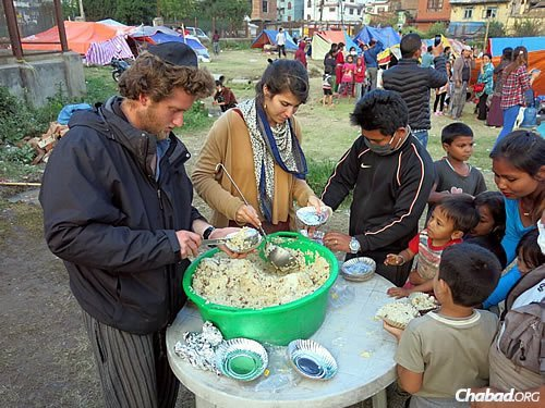 "Serving a hot dish of ""dal bhat,"" a lentils-and-rice local stapled, and pita bread in Nepal. (Photo: David Karsenty/Chabad of Nepal)"