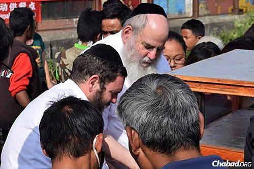On the sixth day of the humanitarian crisis in Nepal, Chabad's efforts have been focused on providing aid to thousands of people who have lost everything in the rubble. Rabbi Chezky Lifshitz, left, and Rabbi Moshe Kotlarsky, center, help distribute food at a makeshift camp in Kathmandu. (Photo: Chabad.org/Nepal)