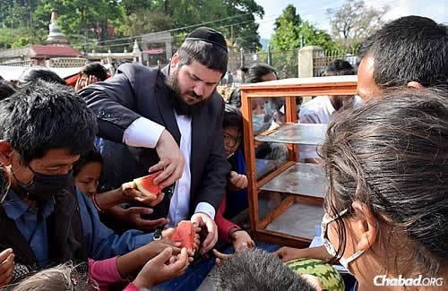 Rabbi Mendy Kotlarsky serves up slices of fresh watermelon. (Photo: Chabad.org/Nepal)