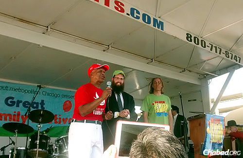 On stage at Thursday-night's Great Family Festival are, from left, 80-year-old Jesse White, a man of many talents and Illinois secretary of state; Rabbi Meir Moscowitz, regional director of Lubavitch Chabad of Illinois; and stand-up comedian and MC for the evening Brett Walkow.